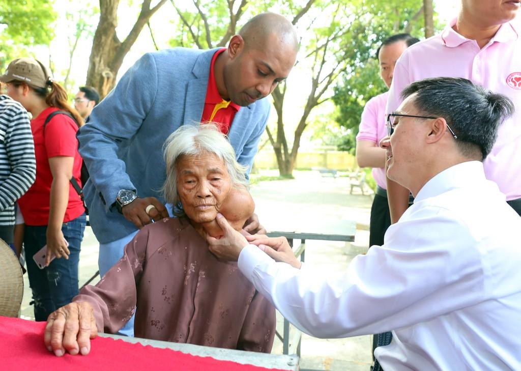 GS, TS Trần Văn Thuấn, Chủ tịch Hội Thầy thuốc Trẻ Việt Nam trực tiếp khám cho bà Cao Thị Cách, 85 tuổi. Bà Cách bị u máu từ nhỏ, gần đây khối u lớn, che gần kín cổ và một phần mặt khiến cuộc sống thường nhật vô cùng khó khăn, đau đớn.