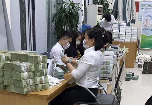 Cán bộ ngân hàng đếm tiền thu giữ được của Phan Sào Nam tại Quảng Ninh. Ảnh: CAND