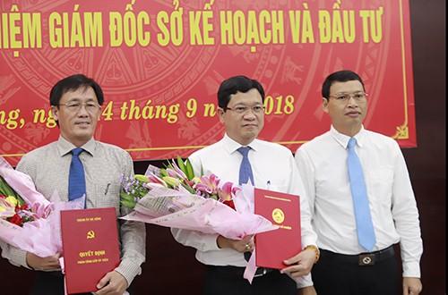 Từ trái qua: Ông Trần Văn Sơn và ông Trần Phước Sơn nhận quyết định và hoa chúc mừng từ Phó chủ tịch Đà Nẵng Hồ Kỳ Minh.