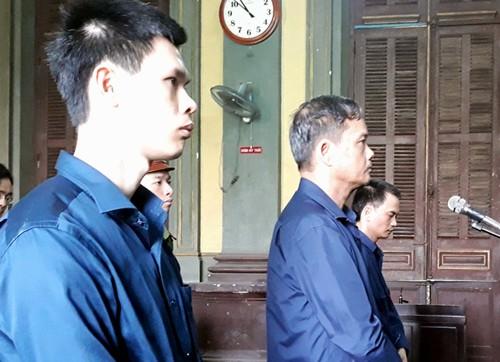 Bình (giữa) cùng các bị cáo nghe tuyên án.