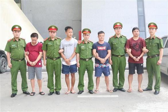 Các đối tượng bị truy nã người Trung Quốc được trao trả cho Công an Trung Quốc - Ảnh: TTXVN