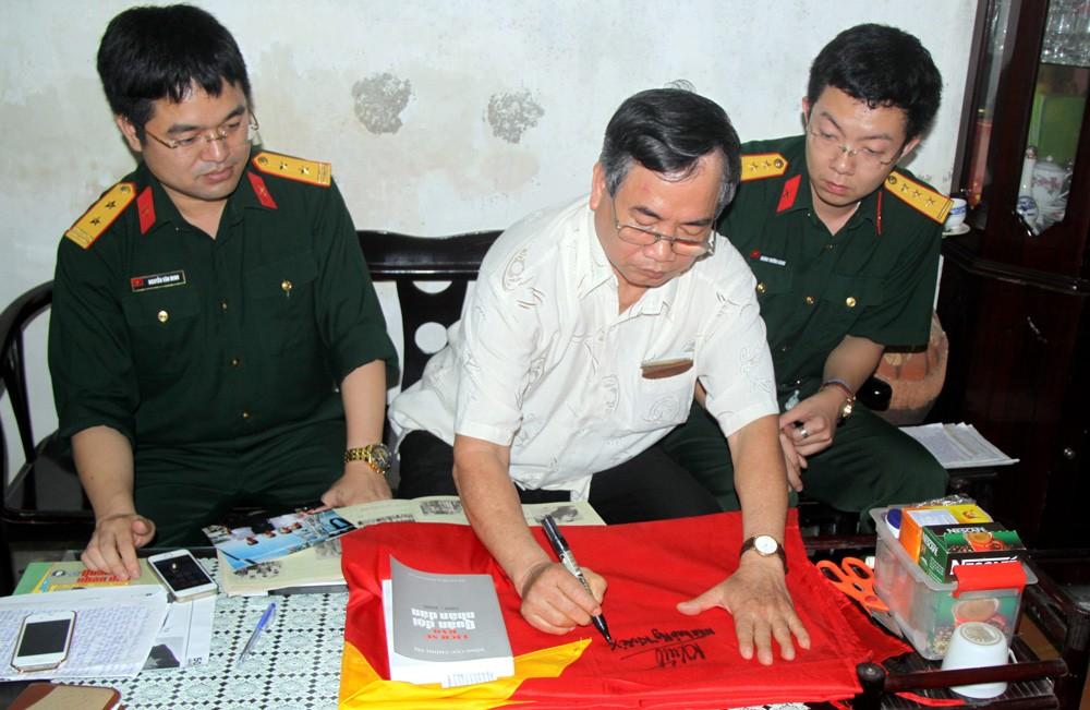 Nhà báo Nguyễn Khắc Xuể ký tặng lên lá Quốc kỳ gửi bộ đội Trường Sa