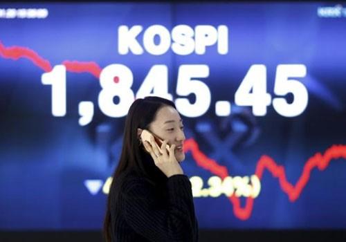 Một phụ nữ nói chuyện điện thoại trước tấm biển điện tử chạy chỉ số chứng khoán KOSPI ở Sở chứng khoán Hàn Quốc tại thủ đô Seoul ngày 21/1/2016. Ảnh:Reuters.
