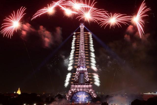 Trước màn trình diễn pháo hoa vào tối qua, một lễ duyệt binh hoành tráng đã được tổ chức vào chiều ngày 14/7, với sự tham gia của Tổng thống Pháp Emmanuel Macron, các quan chức cấp cao của Pháp và Tổng thống Mỹ Donald Trump, người có chuyến thăm Pháp kéo dài 2 ngày. (Ảnh: AFP)