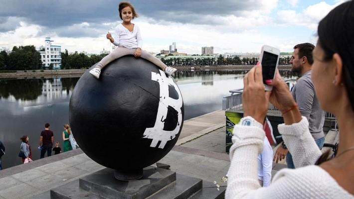 Bé gái tạo dáng để chụp ảnh trên một quả cầu có biểu tượng tiền ảo Bitcoin trên một quảng trường ở Yekaterinburg, Nga - Ảnh: Tass/Getty/CNBC.