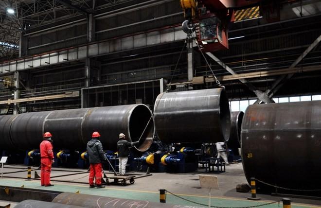 Công nhân làm việc tại nhà máy sản xuất thép tại Thanh Đảo, tỉnh Sơn Đông, Trung Quốc ngày 31/1 vừa qua. (Ảnh: AFP/TTXVN)