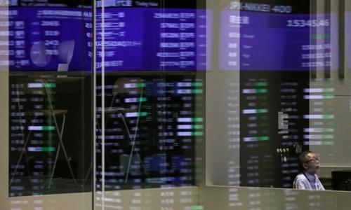 Các chỉ số phản chiếu trên một cửa kính tại Sàn giao dịch Tokyo. Ảnh:Reuters