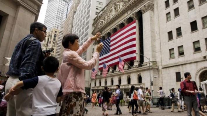 Một du khách Trung Quốc đang chụp ảnh bên ngoài Sở giao dịch chứng khoán New York (NYSE) ở New York, Mỹ - Ảnh: Reuters.