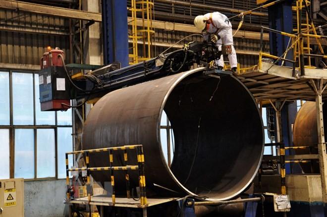 Công nhân làm việc tại nhà máy sản xuất ống thép ở Sơn Đông, Trung Quốc. (Nguồn: AFP/TTXVN)