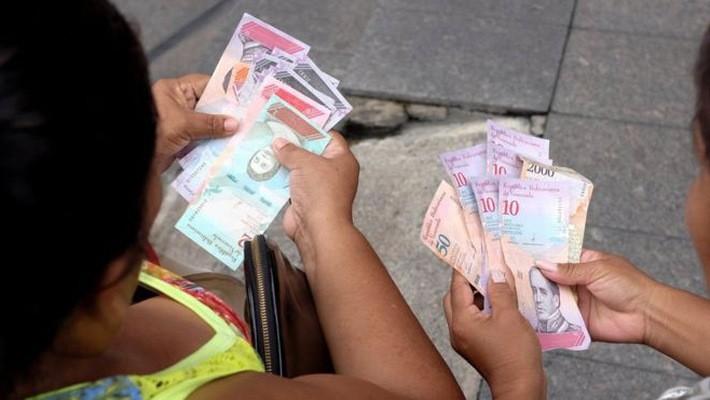 Hai người phụ nữ trên đường phố Caracas ngày 21/8 đang xem những đồng Bolivar mệnh giá mới - Ảnh: Reuters.