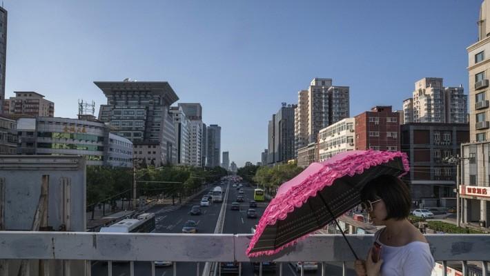 Một phụ nữ cầm ô đi dưới bầu trời trong xanh ở thủ đô Bắc Kinh của Trung Quốc, tháng 7/2018 - Ảnh: Bloomberg.