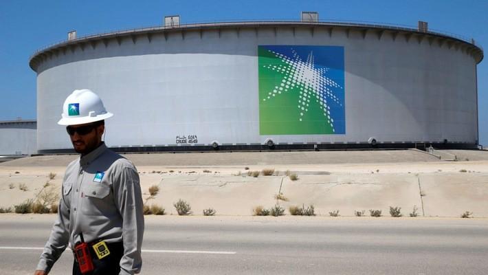 Một công nhân đi qua một bể chứa dầu tại nhà máy lọc dầu Ras Tanura của Saudi Arabia - Ảnh: Reuters/CNBC.