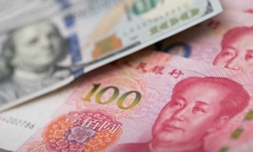 Đồng 100 USD của Mỹ và 100 NDT của Trung Quốc. Ảnh:AFP