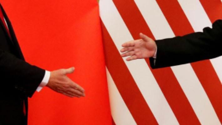 Tổng thống Mỹ Donald Trump và Chủ tịch Trung Quốc Tập Cận Bình đưa tay để bắt tay nhau tại Đại lễ đường Nhân dân ở Bắc Kinh trong chuyến thăm Trung Quốc vào tháng 11/2017 của ông Trump - Ảnh: Reuters.
