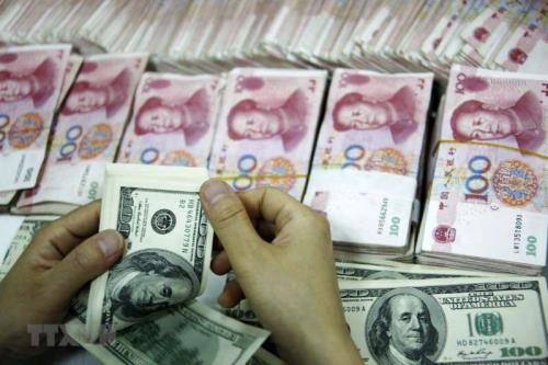 Đồng tiền giấy 100 USD Mỹ và đồng 100 nhân dân tệ. Ảnh: AFP/ TTXVN)