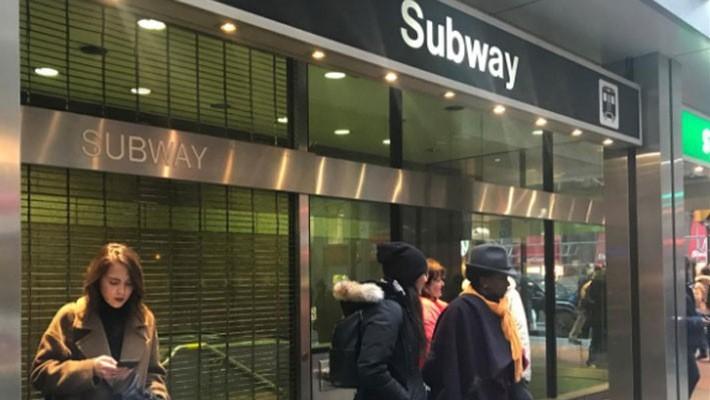 Hành khách đứng ngoài một nhà ga tàu điện ngầm ở Toronto, Canada, sau khi nhà ga này nhận được lời đe dọa đánh bom ngày 13/12 - Ảnh: Reuters.