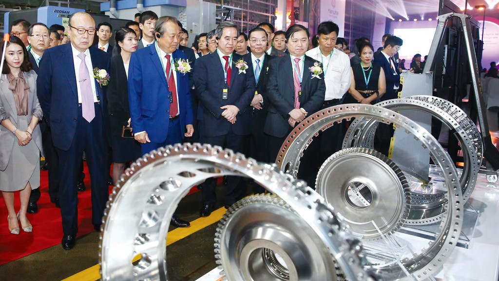 Phó Thủ tướng Trương Hòa Bình cùng các đại biểu tham quan dây chuyền sản xuất của Nhà máy Hanwha Aero Engines tại Khu công nghệ cao Hòa Lạc. Ảnh: Lê Tiên