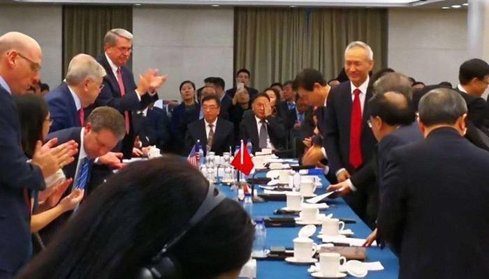 Bức ảnh đăng trên tài khoản Twitter của tờ Wall Street Journal cho thấy Phó thủ tướng Trung Quốc Lưu Hạc (đứng bên phải, cà vạt đỏ) ghé vào phòng đàm phán - Ảnh: Twitter.