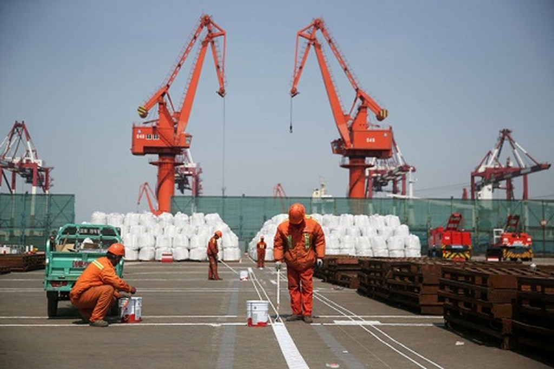 Công nhân đang sơn lại nền tại một cảng của Thanh Đảo, Sơn Đông, Trung Quốc. Ảnh:Reuters
