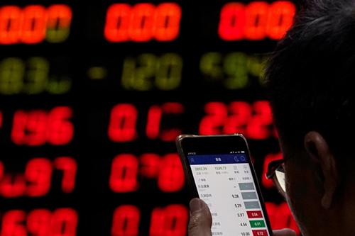 Nhà đầu tư tại một công ty môi giới chứng khoán ở Thượng Hải. Ảnh:Reuters