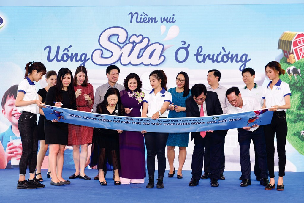 """Các đại biểu cùng ký tên lên bảng tượng trưng với thông điệp """"Hành động để mỗi trẻ em Việt Nam đều được uống sữa mỗi ngày"""""""