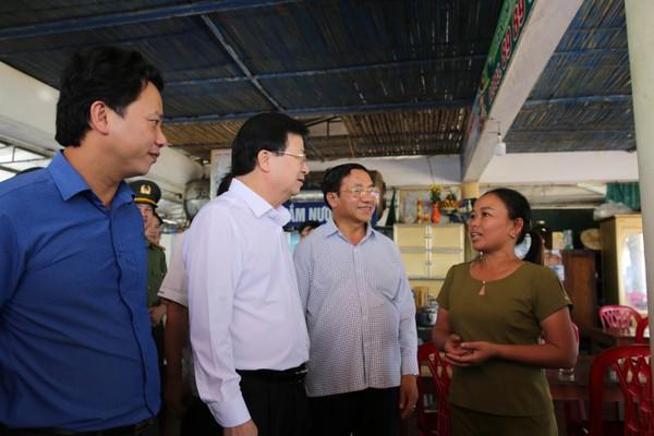Phó Thủ tướng trò chuyện với chủ cơ sở kinh doanh dịch vụ du lịch tại bãi biển Thiên Cầm. Ảnh: VGP