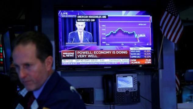 Một nhà giao dịch làm việc trên sàn NYSE ở New York, Mỹ ngày 13/6 trong lúc màn hình TV đang phát sóng tuyên bố nâng lãi suất của FED - Ảnh: Reuters.