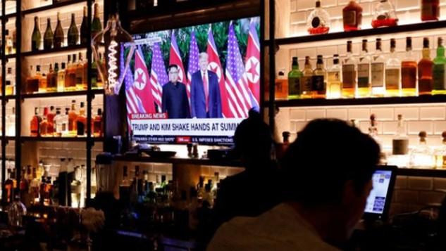Màn hình TV phát sóng bản tin về cuộc gặp thượng đỉnh Mỹ-Triều trong một quán bar ở Manhattan, New York hôm 12/6 - Ảnh: Reuters.