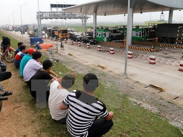 Trước đó, khi dự án đi vào thu phí, nhiều chủ xe đã huy động ôtô chặn tại hai đầu trạm thu phí để phản đối mức thu không hợp lý. Ảnh: TTXVN