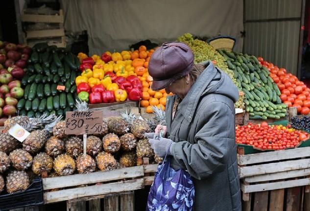 Một người dân đứng trước quầy hàng thực phẩm ở Saint Petersburg - Ảnh: Bloomberg