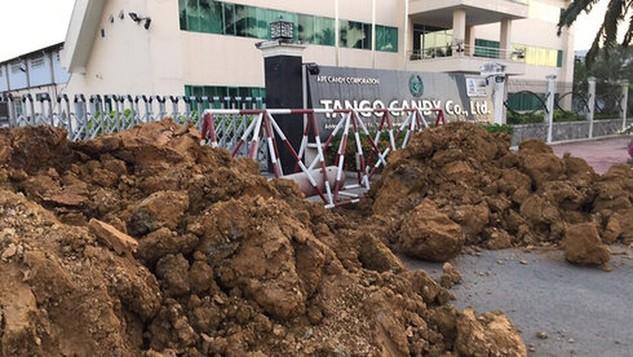 Người của KCN Tân Đức dựng rào chắn, đào ống cắt nguồn nước vào doanh nghiệp vào chiều 17-3 và sau đó tiếp tục đổ đất chắn lối đi - Ảnh: CTV