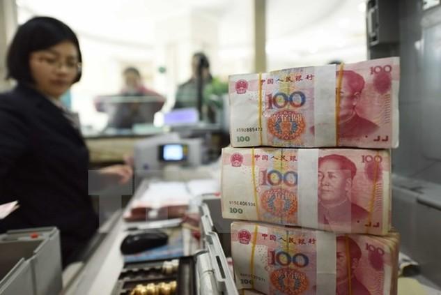 Nhân viên kiểm đồng nhân dân tệ tại một ngân hàng ở tỉnh Giang Tô. (Nguồn: AFP/TTXVN)