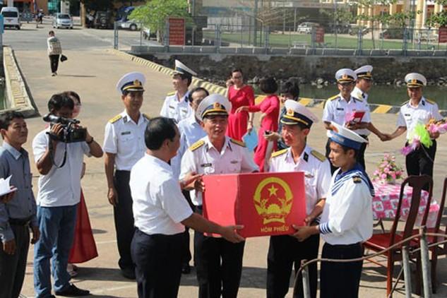 Các cán bộ, chiến sĩ Vùng 2 Hải quân nhận hòm phiếu bầu cử từ ông Mai Ngọc Thuận, Bí thư Thành ủy TP Vũng Tàu, tỉnh Bà Rịa - Vũng Tàu (hàng trước, bên trái), để phục vụ bầu cử sớm trên biển (Ảnh: Người lao động)