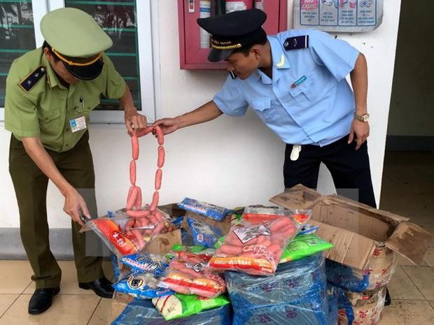 Lực lượng liên ngành thành phố Móng Cái bắt giữ lô hàng thực phẩm nhập lậu không rõ nguồn gốc. (Ảnh: Văn Đức/TTXVN)