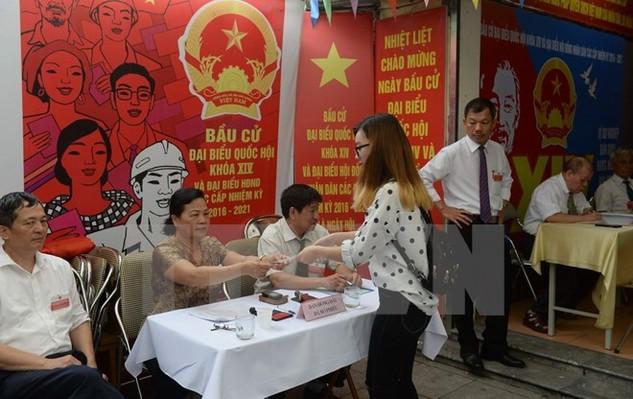 Cử tri Việt Nam nhận phiếu bầu tại một điểm bầu cử ở thủ đô Hà Nội ngày 22/5. (Ảnh: AFP/TTXVN)