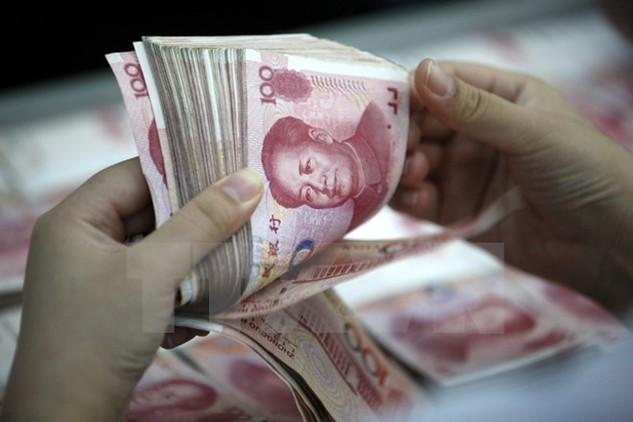 Kiểm tiền mệnh giá 100 nhân dân tệ tại chi nhánh ngân hàng ở Hoài Bắc, tỉnh An Huy, Trung Quốc. (Nguồn: EPA/TTXVN)