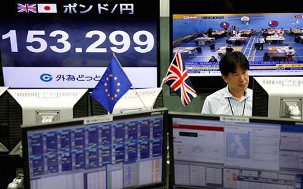 Một nhà giao dịch tiền tệ ở Tokyo theo dõi kết quả cuộc trưng cầu dân ý ở Anh hôm 24/6. Màn hình bên trái hiển thị tỷ giá đồng Bảng Anh so với Yên Nhật - Ảnh: Reuters/CNBC.