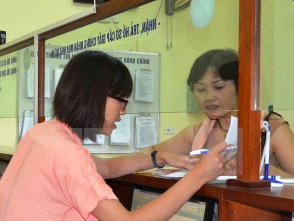 Hướng dẫn thủ tục cho người dân tại bộ phận một cửa Văn phòng Đăng ký đất đai Hà Nội. (Ảnh: Đỗ Phương Anh/TTXVN)