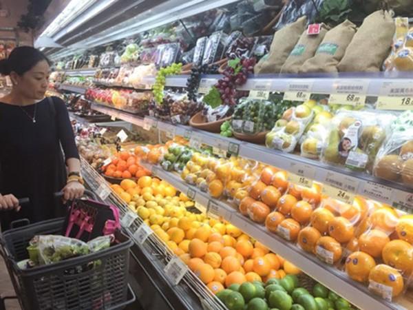 Một khách hàng đang xem hoa quả nhập khẩu tại siêu thị ở Thượng Hải. Ảnh:Nikkei