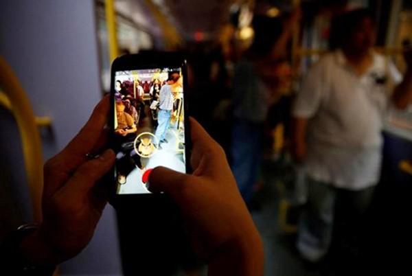 Một người chơi Pokemon Go trên xe bus tại Hong Kong (Trung Quốc). Ảnh: Reuters