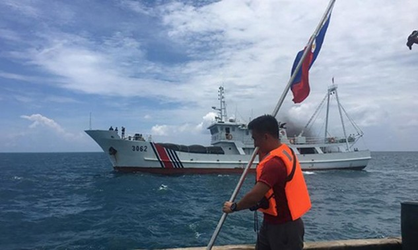 Một nhà hoạt động Philippines giơ cao lá cờ của nước này khi một tàu bảo vệ bờ biển Trung Quốc đi qua. Ảnh:AFP