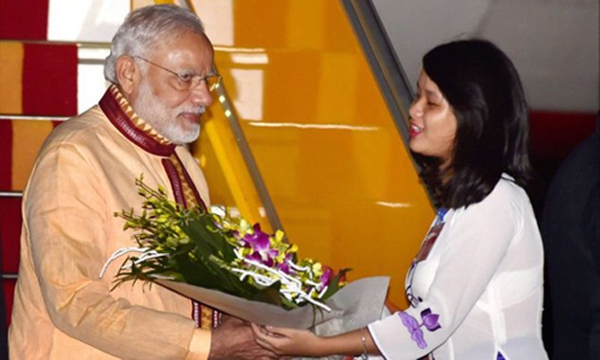 Thủ tướng Ấn Độ Narendra Modi (trái) nhận hoa khi đặt chân tới sân bay Nội Bài. Ảnh: Rediff