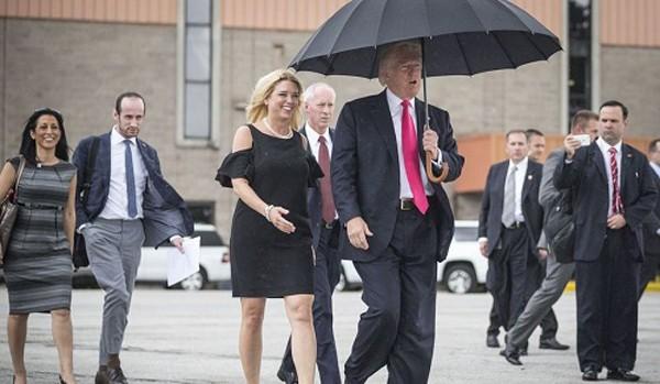 Ông Trump cầm ô che đầu cho mình, mà không che cho bà Bondi bên cạnh. Ảnh:AFP