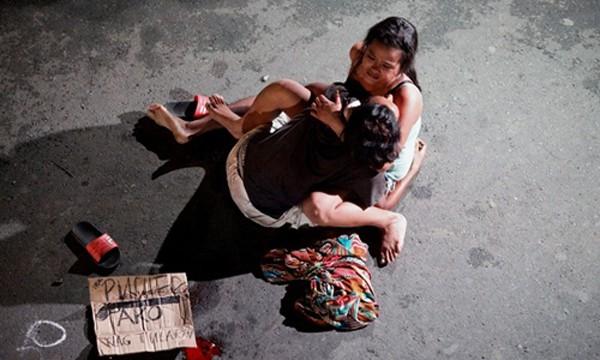 Một phụ nữ ôm chặt xác người chồng bị bắn chết trên đường phố Philippines vì tình nghi buôn bán ma túy. Ảnh:Reuters
