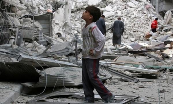 Một cậu bé đứng xem các căn nhà bị hư hại nặng nề sau đợt không kích nhằm vào phe nổi dậy tại Aleppo. Ảnh: Reuters.