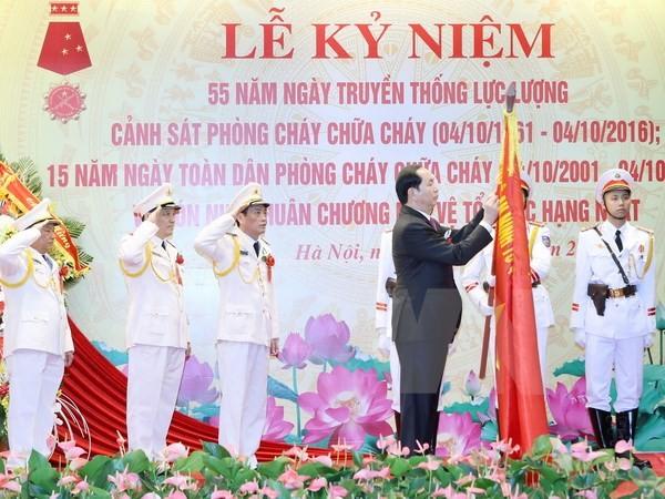 Chủ tịch nước Trần Đại Quang gắn Huân chương Bảo vệ Tổ quốc hạng Nhất lên lá cờ truyền thống của Cục Cảnh sát phòng cháy chữa cháy. (Ảnh: Nhan Sáng/TTXVN)