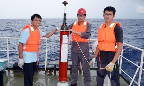 Các nhân viên kỹ thuật Trung Quốc bên cạnh một thiết bị cảm ứng nổi do nước này tự chế tạo. Ảnh: SCMP