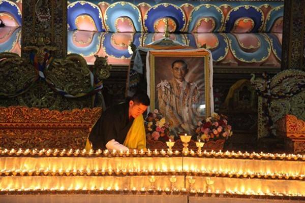 Quốc vương Bhutan Jigme Khesar Namgyel Wangchuck hôm qua thắp nến cạnh chân dung Quốc vương Thái Lan mới qua đời. Ảnh: Facebook