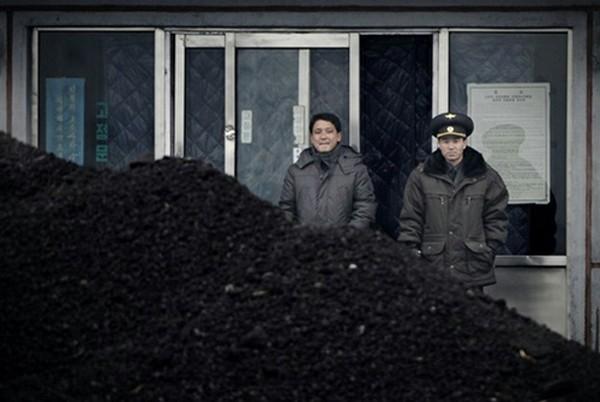 Sĩ quan Triều Tiên (phải) cùng một người đàn ông đứng cạnh đống than bên bờ sông Áp Lục, biên giới với Trung Quốc, năm 2012. Ảnh: AFP.