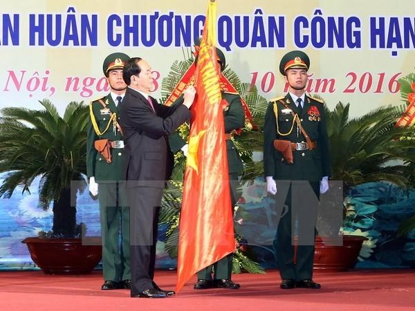 Chủ tịch nước Trần Đại Quang gắn Huân chương Quân công hạng Nhất lên lá cờ truyền thống của lực lượng vũ trang Thủ đô. (Ảnh: Nhan Sáng/TTXVN)